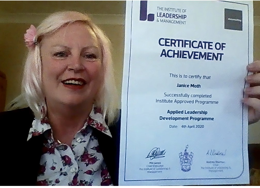 Janice Moth holding up her certificate.